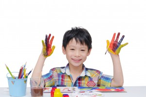 Young Asian boy painting his hands over white background